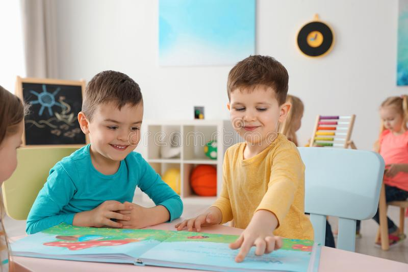 Cute little children reading book together at table indoors royalty free stock image