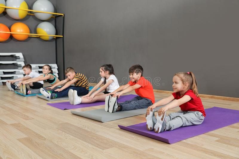 Cute little children sitting on floor and doing physical exercise. Healthy lifestyle stock photo