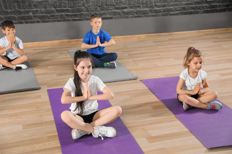 Cute little children sitting on floor and doing physical exercise in school gym royalty free stock photo