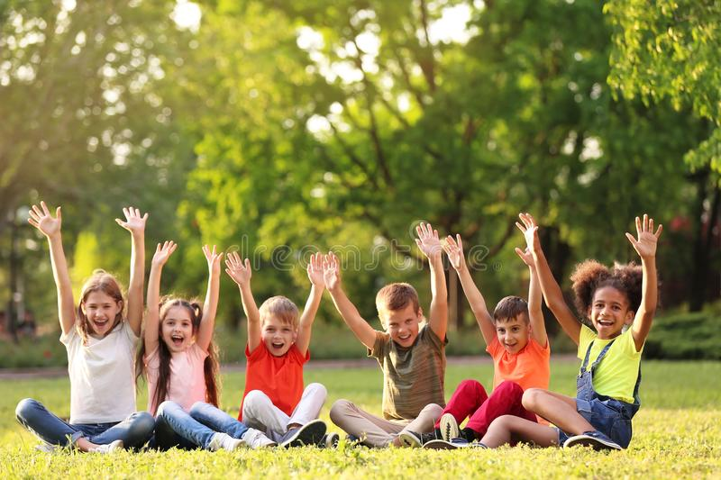 Cute little children sitting on grass outdoors royalty free stock photo