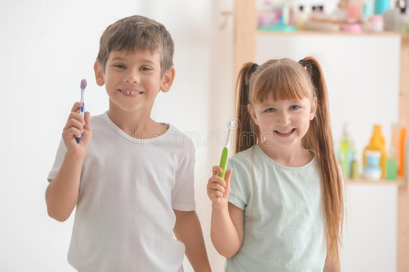 Cute little children with toothbrushes in bathroom stock photo