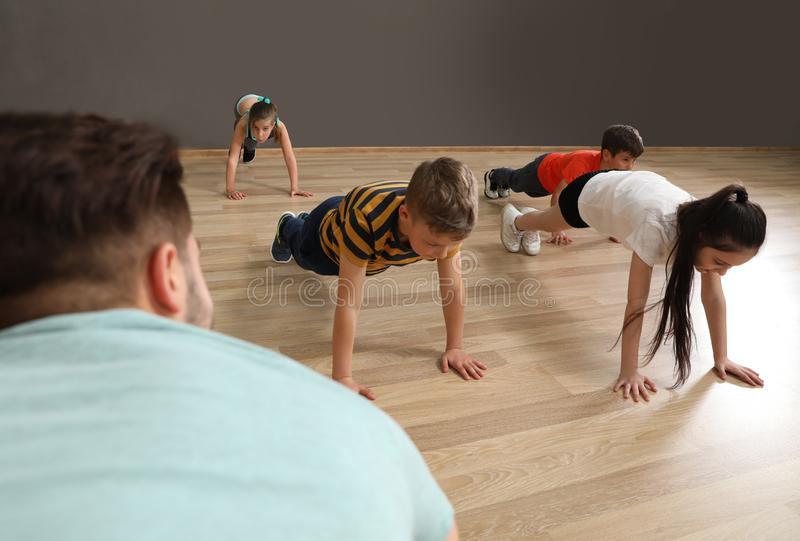 Cute little children and trainer doing physical exercise in school gym royalty free stock photography