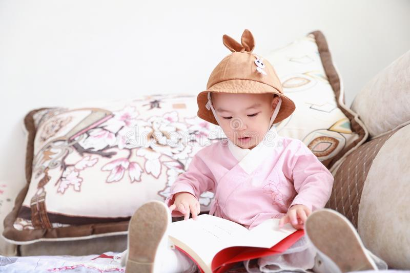 Asian Chinese Baby girl With a hat reading book on sofa royalty free stock images