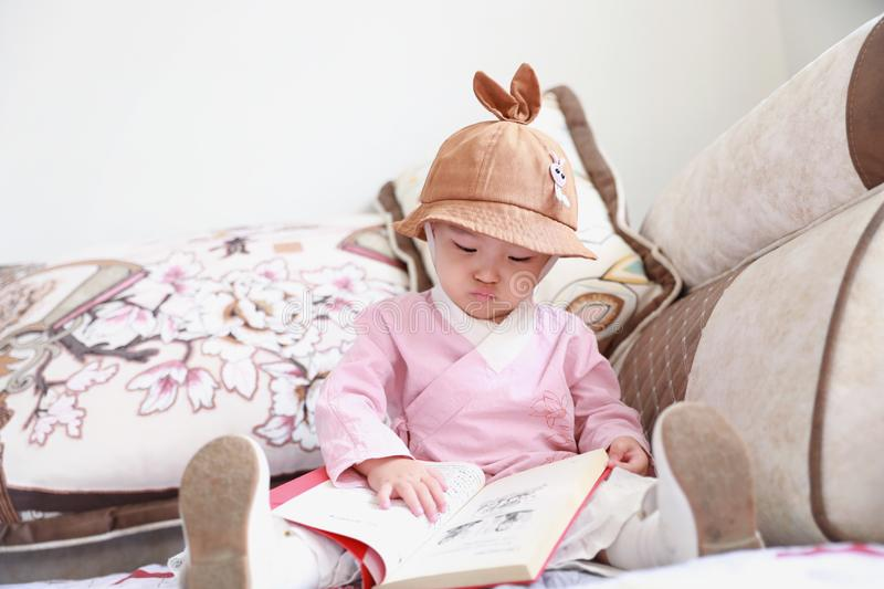 Asian Chinese Baby girl With a hat reading book on sofa royalty free stock photos
