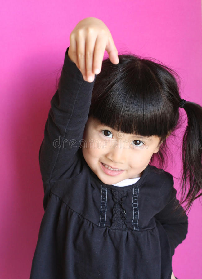 Cute little chinese asian girl with arm in air. Cute little chinese asian girl arm in air with pink backround royalty free stock photo