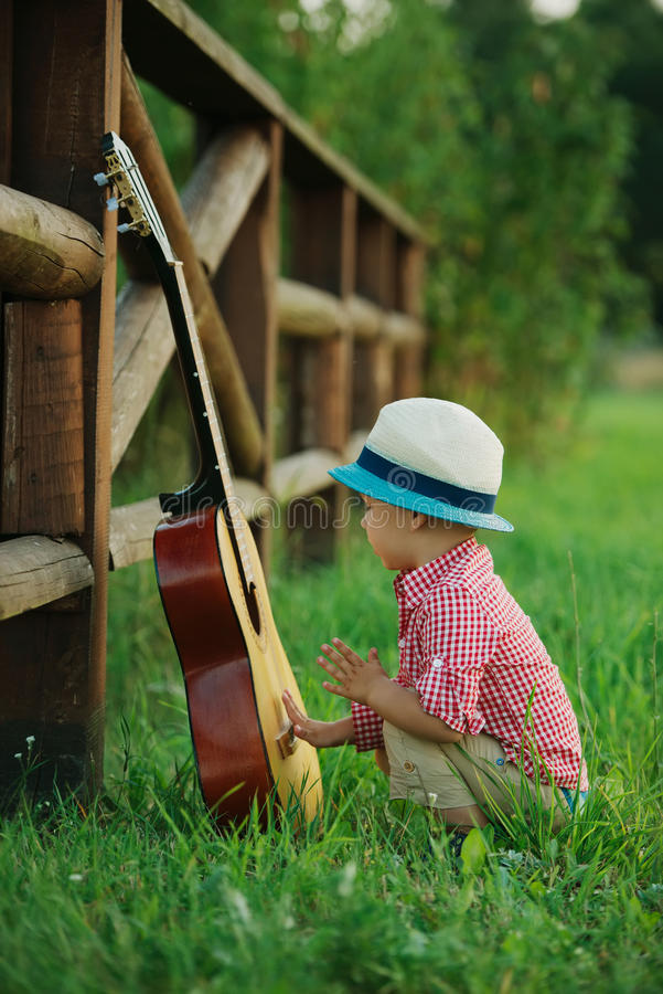 Cute little cowboy playing guitar stock image
