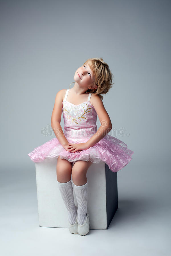 Cute little dancer sitting on cube in studio stock images