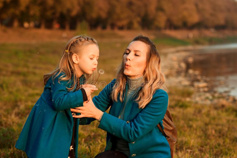 Cute little daughter blowing dandelion flower in a park. Happy mother and child girl having fun together outdoors stock photography