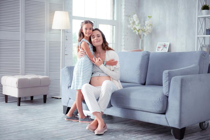 Cute little daughter coming and hugging her caring pregnant mom royalty free stock images