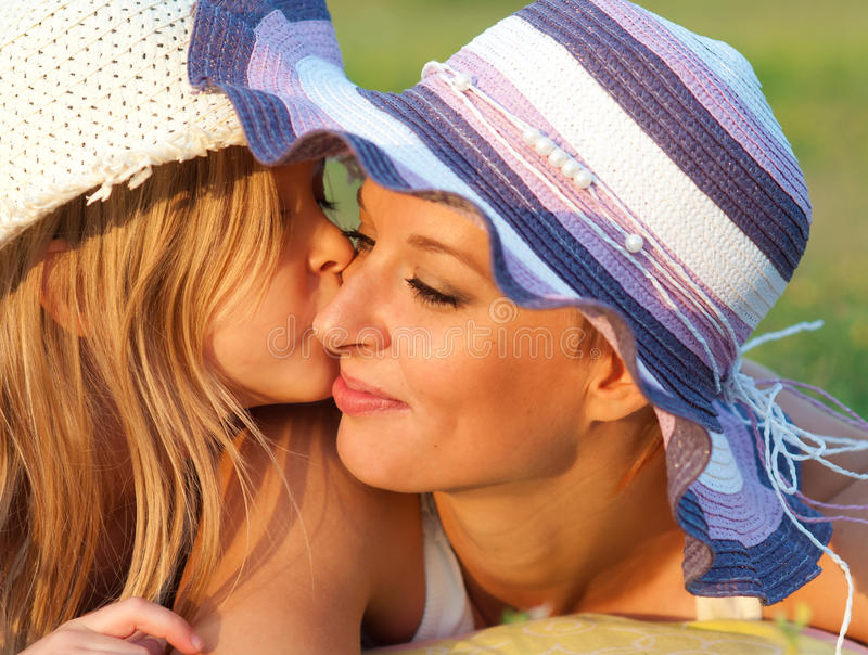 Cute little daughter kissing her mother royalty free stock photography