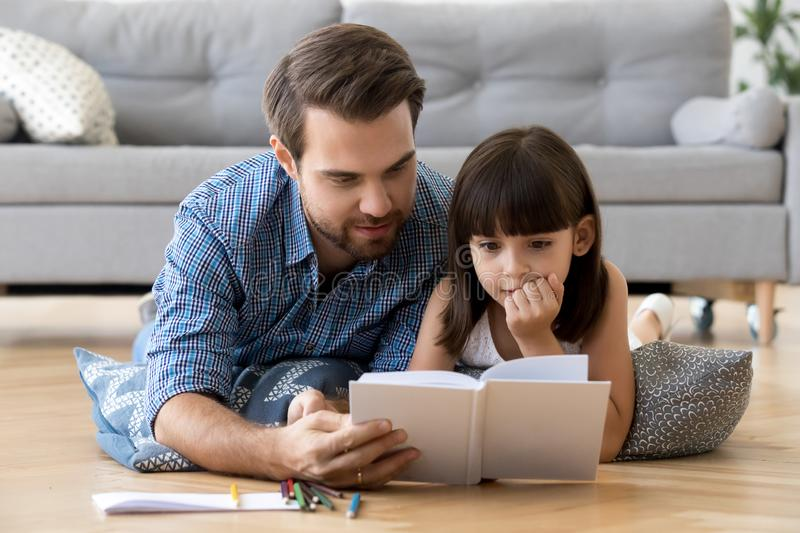 Cute little daughter listening to dad reading book at home stock photos