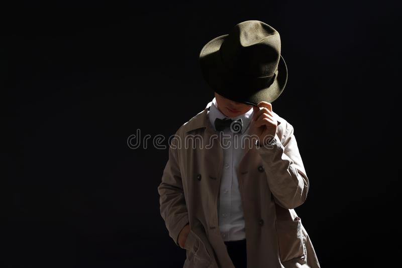 Cute little detective on dark background stock photo