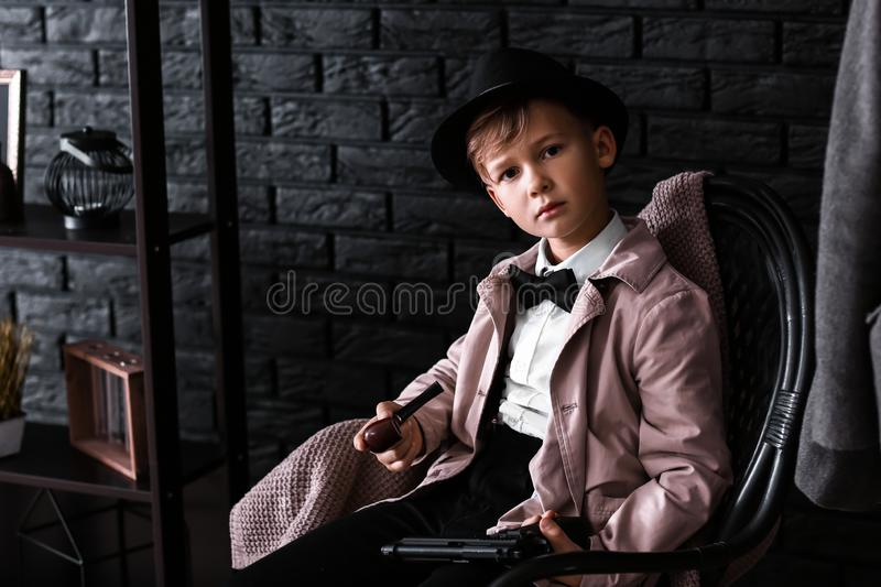 Cute little detective with pipe sitting in armchair royalty free stock photography