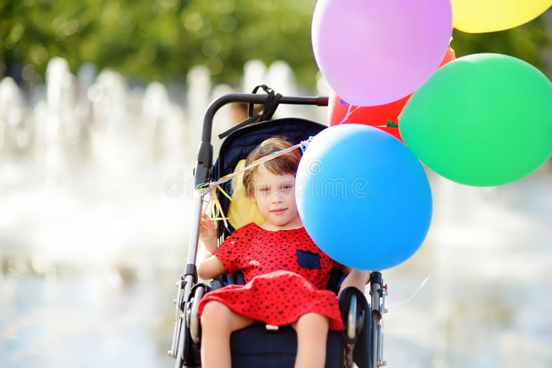 Cute little disabled girl in a wheelchair celebrate birthday or walking in the Park summer. Child cerebral palsy. Inclusion. Family with disabled kid stock image