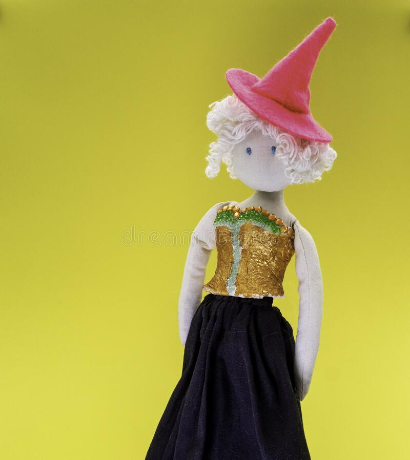 Cute little doll witch with pink witch hat and white curly hair stock images