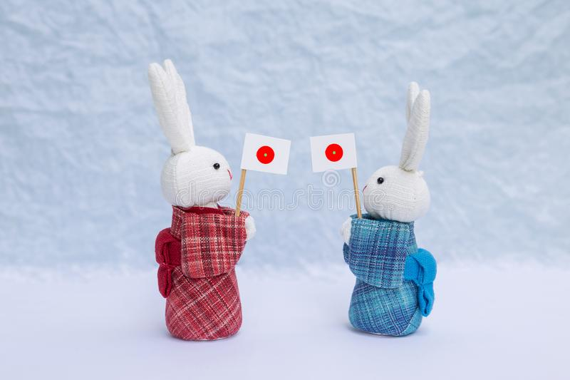 Cute little fabric rabbit doll in red and blue traditional Japanese dress holding Japan flag over blurred white background. Decoration object, Japan tourism royalty free stock photography