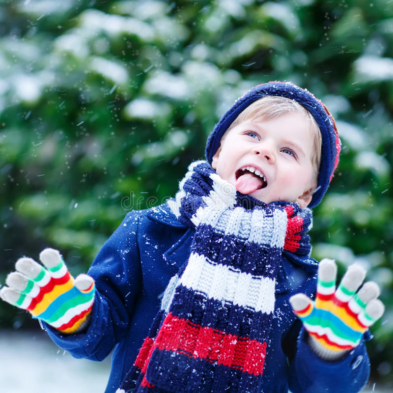 Cute little funny boy in colorful winter clothes having fun with royalty free stock photo
