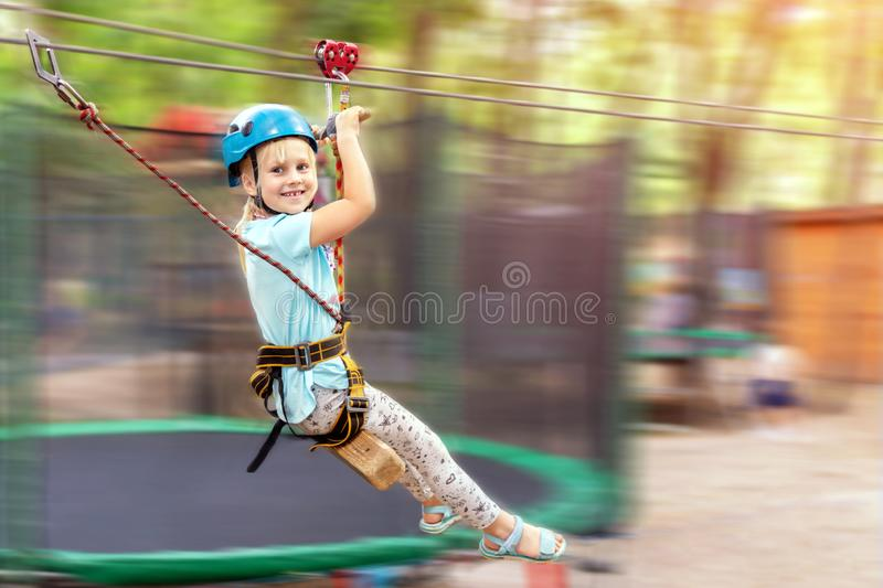 Cute little funny caucasion blond girl in helmet having fun riding rope zipline in adventure park. Children outdoor extreme sport. Activities concept royalty free stock images