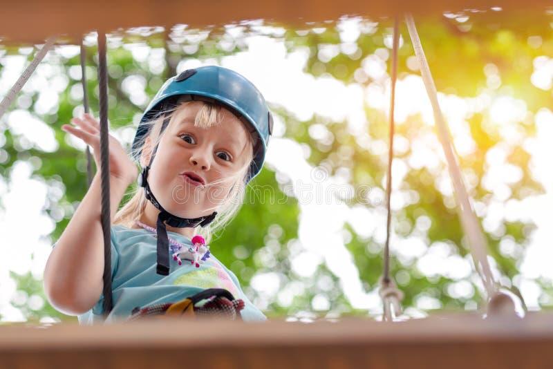 Cute little funny caucasion blond girl in helmet having fun walking by rope suspension bridge in adventure park. Children outdoor. Extreme sport activities stock photo