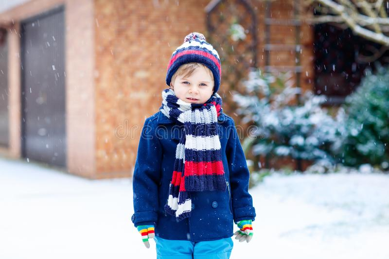 Cute little funny child in colorful winter fashion clothes having fun and playing with snow, outdoors during snowfall royalty free stock images