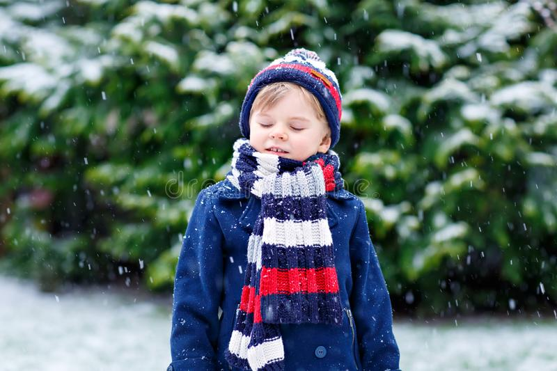 Cute little funny child in colorful winter fashion clothes having fun and playing with snow, outdoors during snowfall stock images