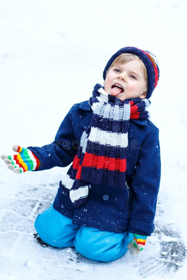 Cute little funny kid boy in colorful winter fashion clothes having fun and playing with snow, outdoors during snowfall stock image
