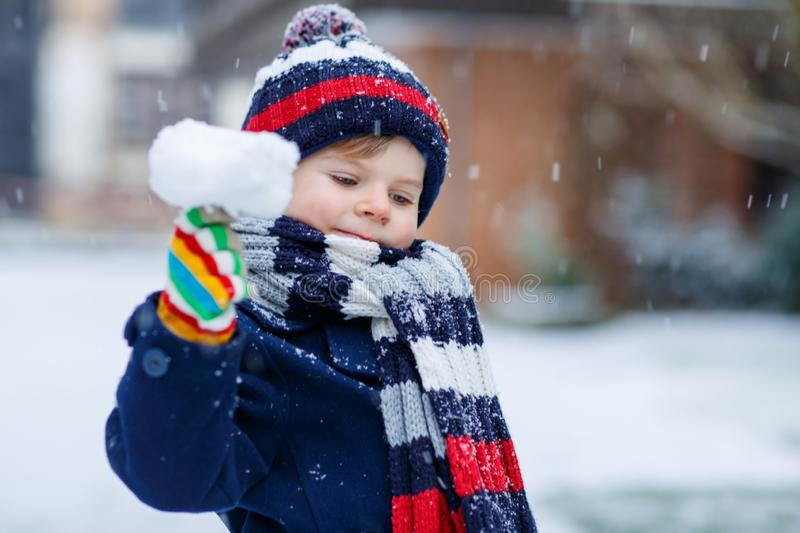 Cute little funny kid boy in colorful winter fashion clothes having fun and playing with snow, outdoors during snowfall. Cute little funny child in colorful stock photography