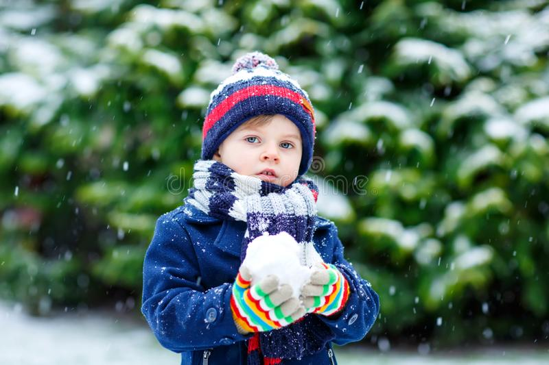 Cute little funny kid boy in colorful winter fashion clothes having fun and playing with snow, outdoors during snowfall stock photos