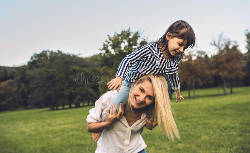 Cute little funny daughter on a piggy back ride with her smiling mother. Loving woman and her little girl playing in the park. Mom stock images