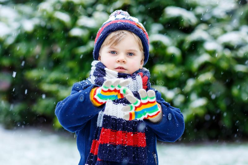 Cute little funny kid boy in colorful winter fashion clothes having fun and playing with snow, outdoors during snowfall royalty free stock photography