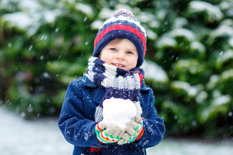 Cute little funny kid boy in colorful winter fashion clothes having fun and playing with snow, outdoors during snowfall stock photography