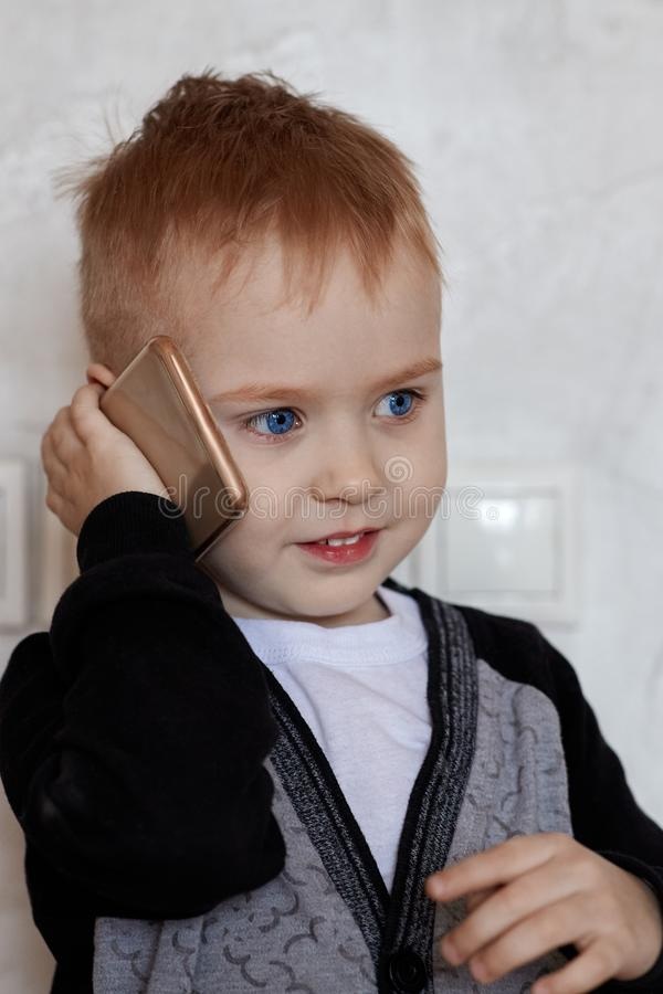 Cute little ginger baby boy with blue eyes speaks through mobile phone, smiling. Children and modern technology concept. royalty free stock images