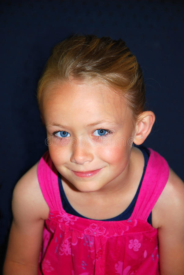 Cute little girl. Studio portrait of a young cute little Caucasian blond girl with blue eyes and happy smiling facial expression looking up in front of dark blue royalty free stock photos