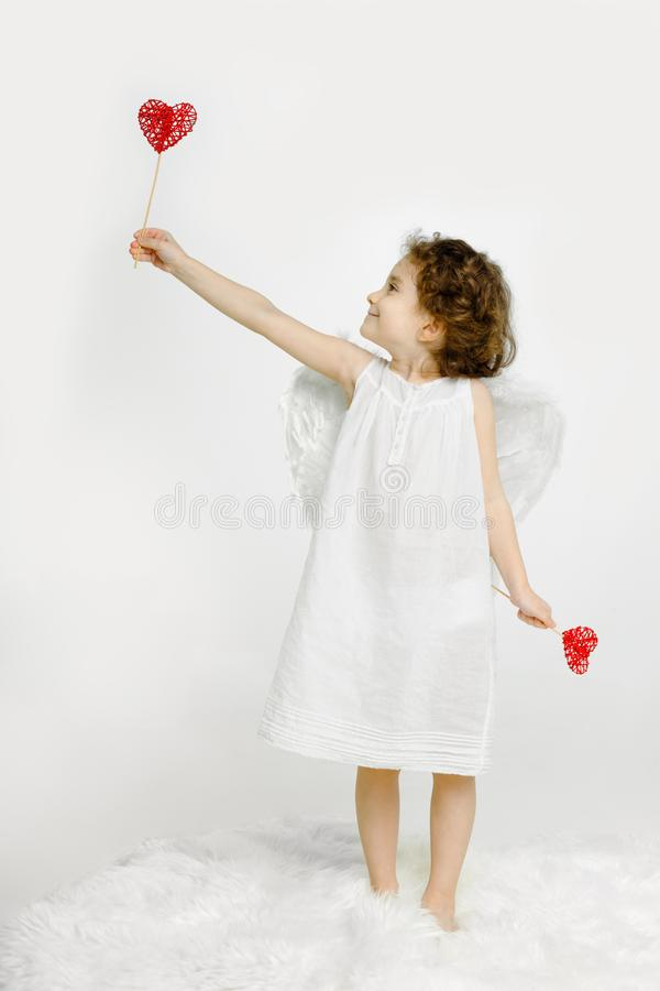 Cute little girl in angel look, in white dress and wings, holding a red heart in hands, looking in profile. royalty free stock photos