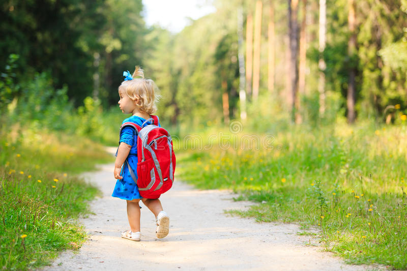 Cute little girl with backpack in summer forest stock photography