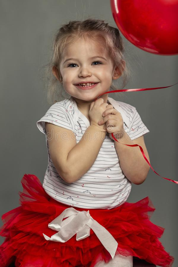Cute little girl with a balloon in her hands laughs. close-up. Gray background stock image