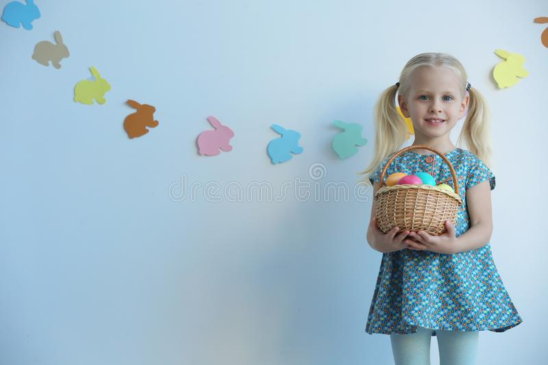 Cute little girl with basket full of Easter eggs stock images