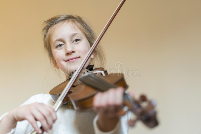 Cute little girl in a beautiful dress playing violin. Joyful and happy emotions. Training. Education. School. Aesthetic training. stock photo