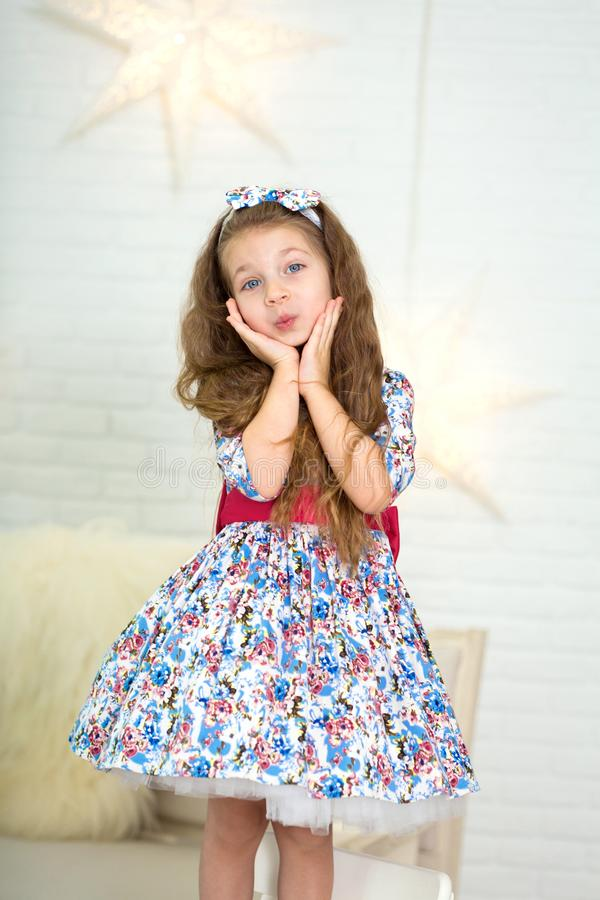 Cute little girl in a beautiful dress presses her hands to her face in surprise stock photography