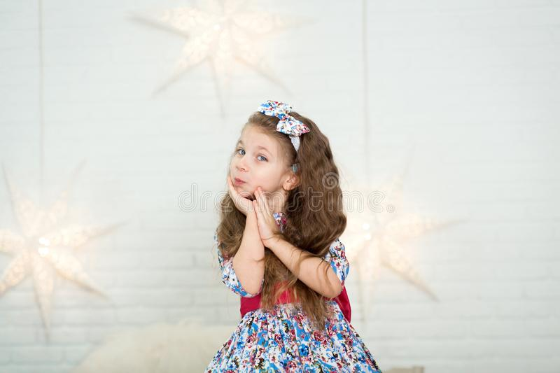 Cute little girl in a beautiful dress presses her hands to her face in surprise royalty free stock images