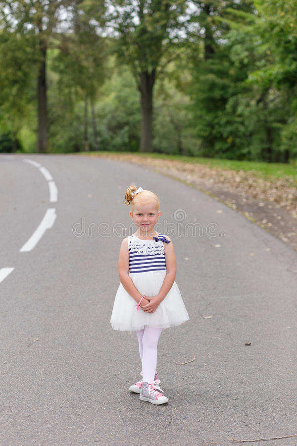 Download A Cute Little Girl In A Beautiful Dress And Sneakers Playing On Stock Photo - Image: 83718810