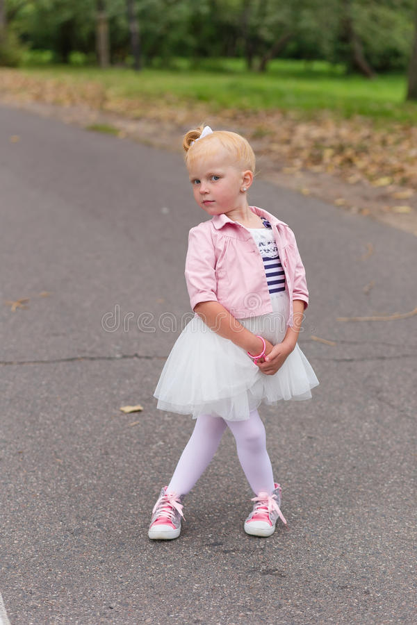 Download A Cute Little Girl In A Beautiful Dress And Sneakers Playing On Stock Photo - Image: 83719616