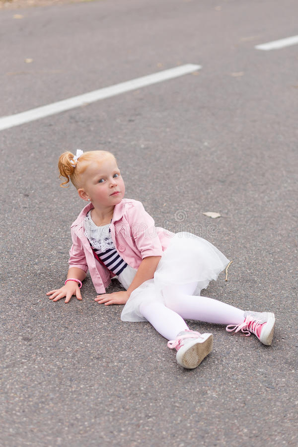 Download A Cute Little Girl In A Beautiful Dress And Sneakers Playing On Stock Photo - Image: 83719664
