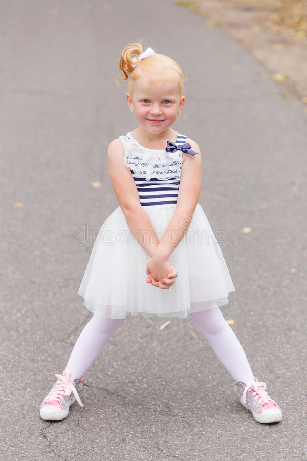 Download A Cute Little Girl In A Beautiful Dress And Sneakers Playing On Stock Photo - Image: 83720038
