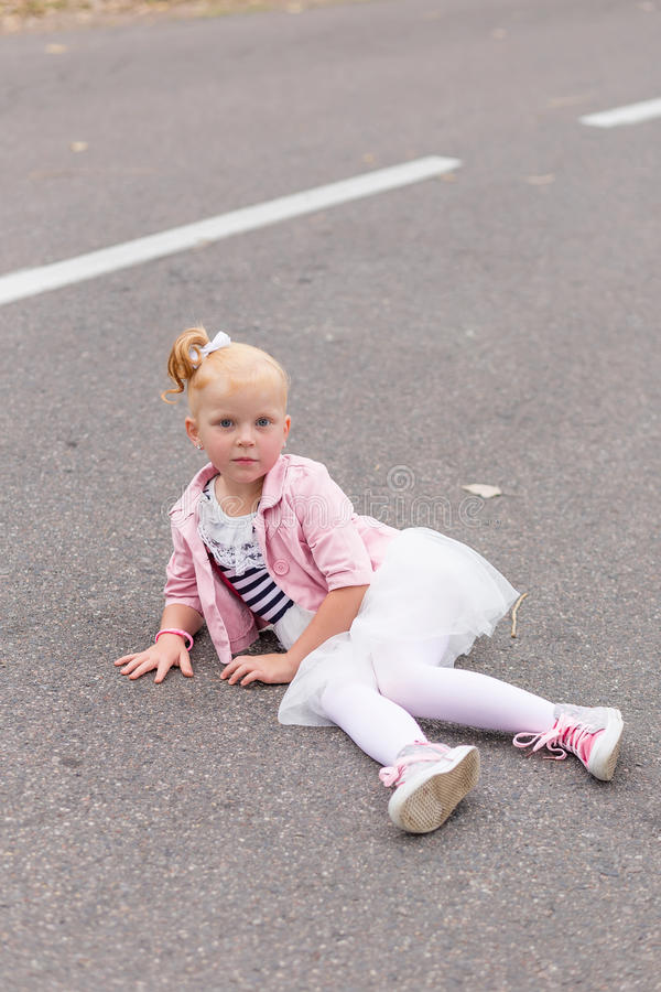 Download A Cute Little Girl In A Beautiful Dress And Sneakers Playing On Stock Photo - Image: 83720128