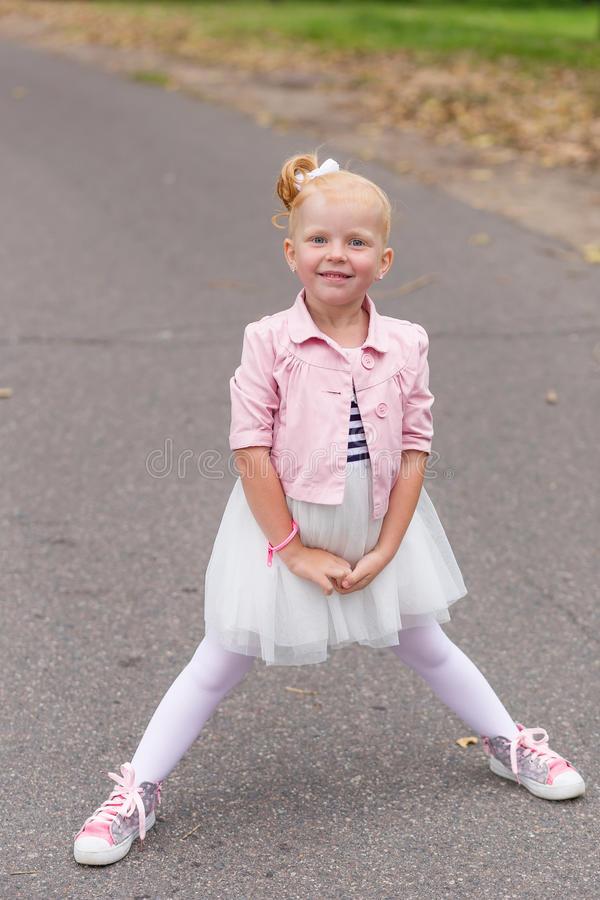 Download A Cute Little Girl In A Beautiful Dress And Sneakers Playing On Stock Photo - Image: 83720496