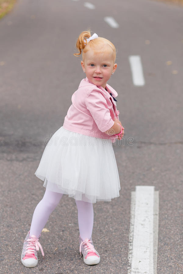 Download A Cute Little Girl In A Beautiful Dress And Sneakers Playing On Stock Photo - Image: 83720604