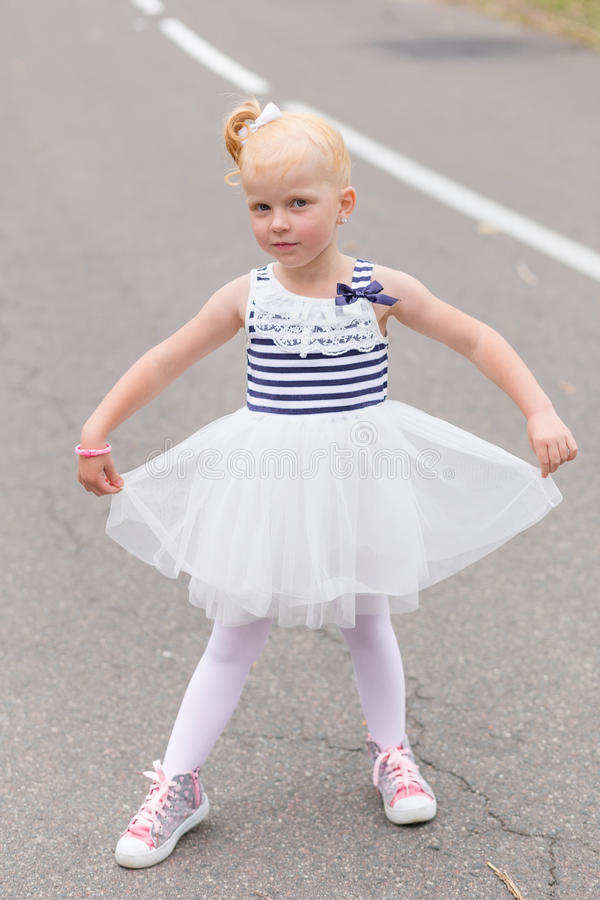 Download A Cute Little Girl In A Beautiful Dress And Sneakers Playing On Stock Photo - Image of risk, child: 83720614