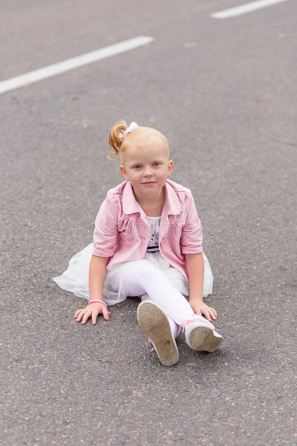Download A Cute Little Girl In A Beautiful Dress And Sneakers Playing On Stock Photo - Image: 83720774