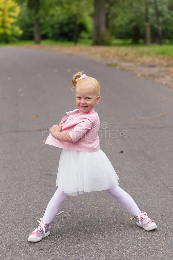 Download A Cute Little Girl In A Beautiful Dress And Sneakers Playing On Stock Photo - Image: 83720792